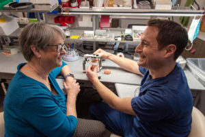 Dental implants Munster staff showing model to patient